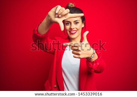 Young beautiful business woman standing over red isolated background smiling making frame with hands and fingers with happy face. Creativity and photography concept. #1453339016