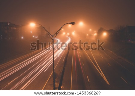 Highway at foggy night with bright trails of light from incoming and outgoing traffic. Transportation, traffic, urbanism and infrastructure concepts. #1453368269