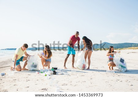 Group of activists friends collecting plastic waste on the beach. People cleaning the beach up, with bags. Concept about environmental conservation and ocean pollution problems #1453369973