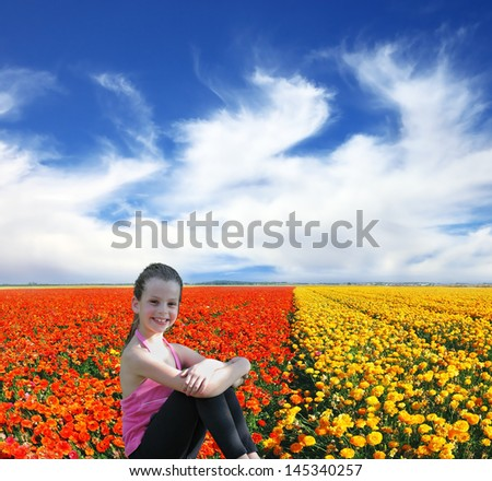 Charming beautiful girl posing and smiling in a field of blossoming yellow and red buttercups #145340257