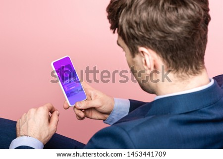 cropped view of businessman using smartphone with shopping app, isolated on pink #1453441709