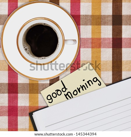 notebook and cup of coffee on picnic tablecloth