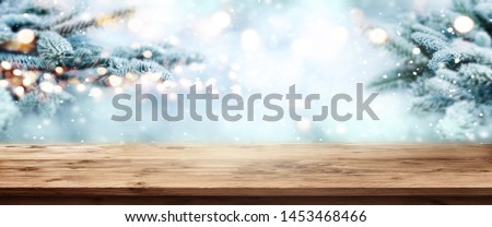 Fir branches in snow with wooden table and festive bokeh at christmas time #1453468466