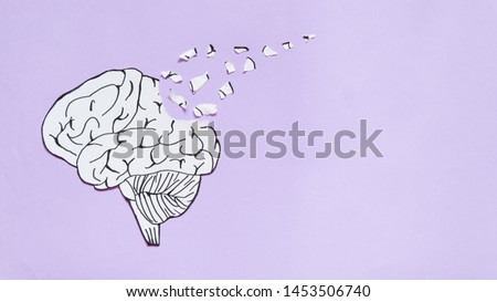 Brain disorder symbol presented by human brain made form paper torn on purple background w/ copy space. Creative idea for Alzheimer's disease, dementia or memory loss. Mental health care concept.