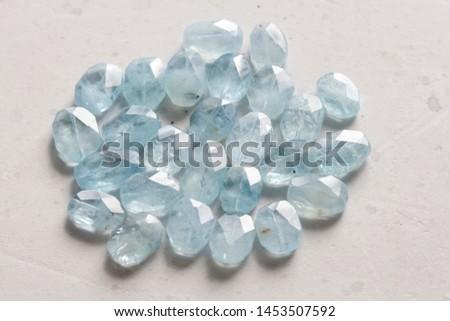Aquamarine stone. Natural stone and aquamarine crystals on a white background. Beautiful aquamarine stones. #1453507592