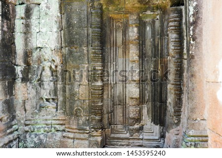 SIEM REAP, CAMBODIA -July 12, 2019: Stone carving on the fake door of Prasat Banteay Kdei, the Buddhist temple built in the 12th century, in the ancient city of Angkor #1453595240