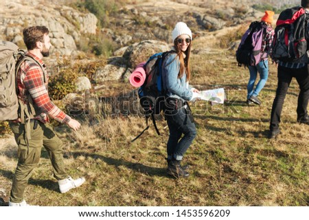 Photo of young group of friends outside in free alternative vacation camping over mountains walking with map.