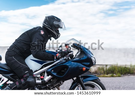 biker rides motorcycle, motorcyclist side view, close up of bike rides motorcycle, motorcyclist side view, close-up, motorcycle racing, motorcycle profile and racer #1453610999