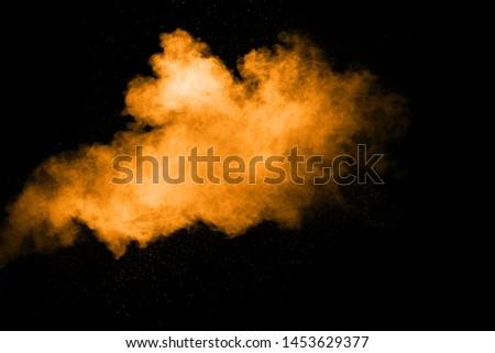 Abstract orange dust explosion on  black background.  Freeze motion of orange powder clouds splash. #1453629377