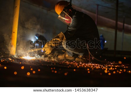 Male worker metal cutting spark on tank bottom steel plate with flash of cutting light close up wear protective gloves and mask in side confined space. #1453638347