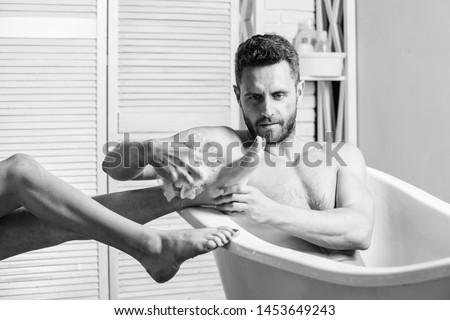 guy wash female legs with foam sponge. macho enjoying bath. Sexy man in bathroom. Sex and relaxation concept. Macho naked in bathtub. Wash off foam with water carefully. man with muscular body. #1453649243