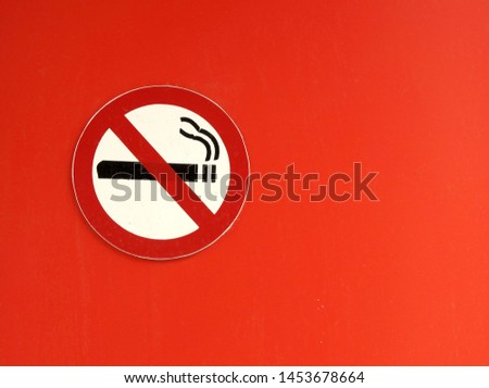 The sign-smoking is prohibited, attached to a bright orange wall. Close-up.