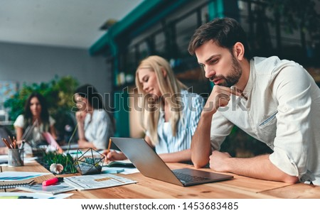 Group of young business people are working together in modern office. Creative people with laptop, tablet, smart phone, notebook. Successful hipster team in coworking. Freelancers. Royalty-Free Stock Photo #1453683485