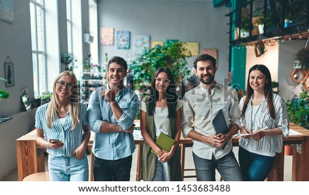 Group of young business people are working together in modern office. Creative people with laptop, tablet, smart phone, notebook. Successful hipster team in coworking. Freelancers. Royalty-Free Stock Photo #1453683488