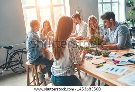 Group of young business people are working together in modern office. Creative people with laptop, tablet, smart phone, notebook. Successful hipster team in coworking. Freelancers. Royalty-Free Stock Photo #1453683500