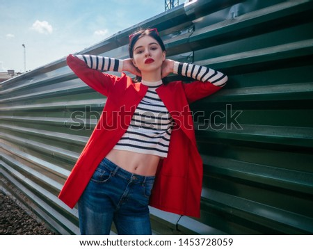 Beautiful glamorous brunete girl in a red jacket posing in the city street. City life on background #1453728059