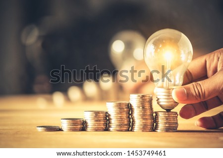Hand holding a light bulb with coins stack. Creative ideas for saving money concept. Money management for the future  #1453749461