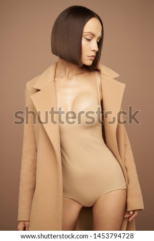 Fashion studio photo of young beautiful lady in beige coat on beige background. Total beige. Fashion look book. Warm Autumn. Warm Spring #1453794728