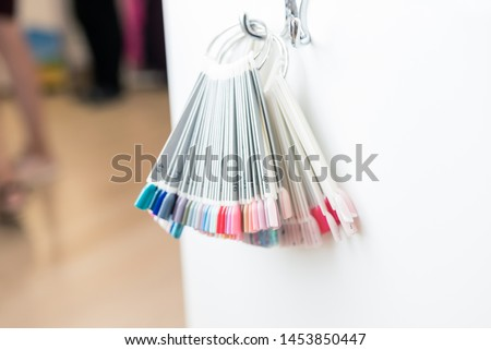 Female hands with a perfect manicure and nail design samples. Beauty salon for nails. Nail polish in different colors. Colorful nail polish #1453850447