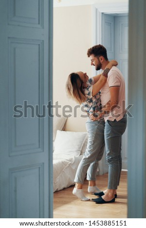 Profile view of loving young couple hugging while standing in their bedroom. View from another room through the doorway #1453885151