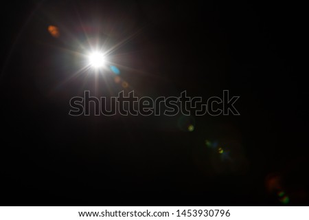 Lens Flare. Light over black background. Easy to add overlay or screen filter over photos. Abstract sun burst with digital lens flare background. Gleams rounded and hexagonal shapes, rainbow halo. #1453930796