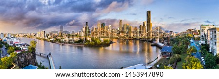 Brisbane river flowing through Brisbane city around CBD under Story bridge in soft morning light after rain - wide aerial panorama. #1453947890