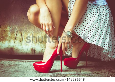 woman legs in red high heel shoes and short skirt outdoor shot against old metal door Royalty-Free Stock Photo #145396549
