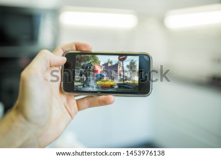 Minsk, Belarus - July 17, 2019: Gamer hands hold a smartphone Apple iPhone SE  with an online game Player's Unknown Battleground, or  PUBG #1453976138
