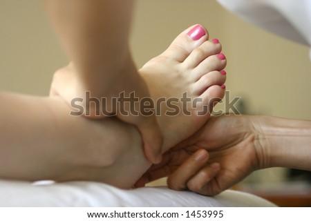 A woman receiving foot reflexology as part of a holistic massage treatment #1453995