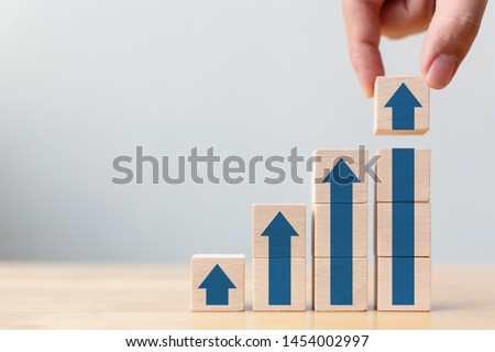 Ladder career path for business growth success process concept.Hand arranging wood block stacking as step stair with arrow up #1454002997