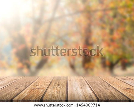 Empty brown wooden table in front of art abstract bokeh background of maple trees in autumn with shiny of sunlight for your display or montage #1454009714