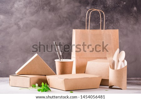Catering and street fast food paper cups, plates and containers. Eco-friendly food packaging and cotton eco bags on gray background with copy space. Carering of nature and recycling concept. #1454056481