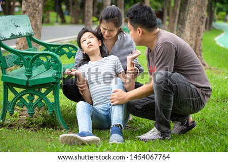 Sick little child girl with epileptic seizures in outdoor park,daughter suffering from seizures,illness with epilepsy during seizure,asian mother,father care of girl patient,brain,family care concept #1454067764