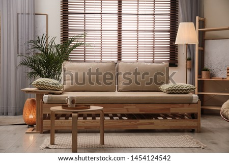 Living room interior with sofa, window blinds and stylish decor elements Royalty-Free Stock Photo #1454124542