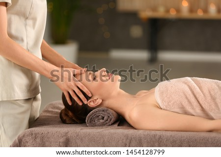 Beautiful young woman enjoying massage in spa salon #1454128799