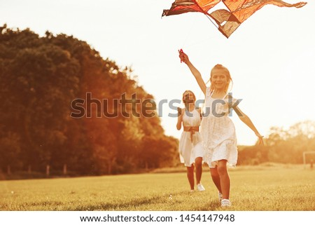 Mother and daughter have fun with kite in the field. Beautiful nature. #1454147948