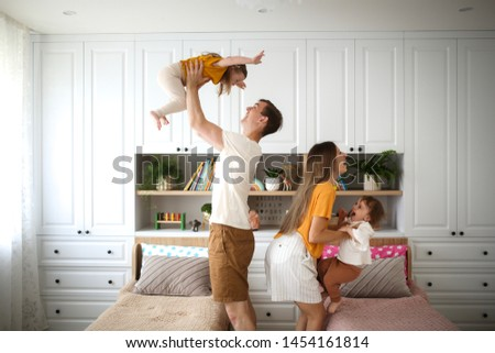 Beautiful Caucasian family with two children in their arms, dad and mom hold two children in the air, a real bright Scandinavian-style interior #1454161814