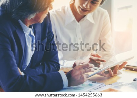 young attractive businesswoman working with touchpad has been guided and consulting by senior colleague #1454255663