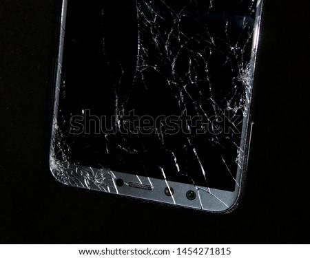 Broken phone on black background. Cracked black screen #1454271815