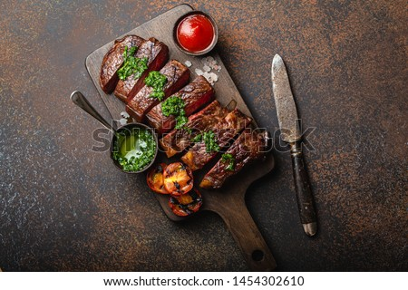 Grilled or fried and sliced marbled meat steak with fork, tomatoes as a side dish and different sauces on wooden cutting board, top view, close-up, stone rustic background. Beef meat steak concept  #1454302610