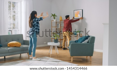 Happy Couple Hanging Picture on the Wall, Boyfriend Moves It, Girlfriend Tells Him when the Frame is Hanging Straight. Funny Moment in Young Couple's Life. Modern Stylish Apartment.