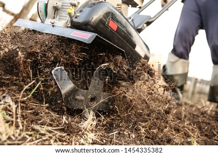 cultivating the land with a gasoline cultivator. knives of a motor-cultivator close up. soil flies out from under the cultivator #1454335382