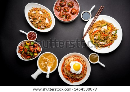 Assorted Indo chinese food in group includes non vegetarian or chicken Schezwan/Szechuan hakka noodles, fried rice, manchurian, egg american chop suey, soup with spoon and chop sticks, selective focus #1454338079