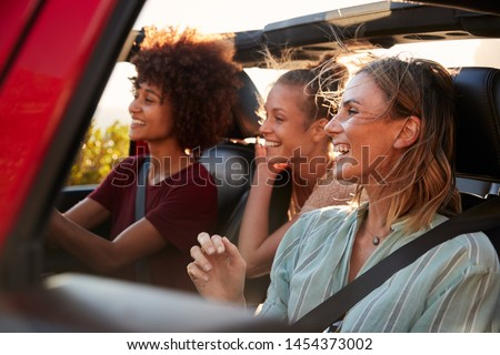 Three millennial female friends on a road trip driving together in an open jeep, close up #1454373002