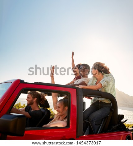 Five young adult friends on a road trip driving in an open top jeep by the sea #1454373017