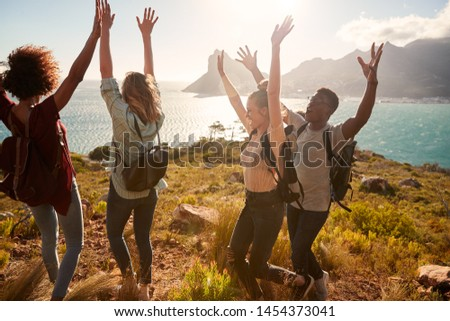 Millennial friends on a hiking trip celebrate reaching the summit, cheering with arms in the air #1454373041