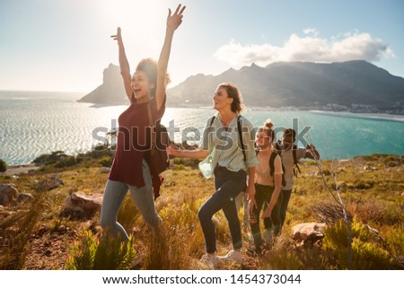 Young adult friends hiking single file uphill celebrate reaching a summit, full length, side view #1454373044