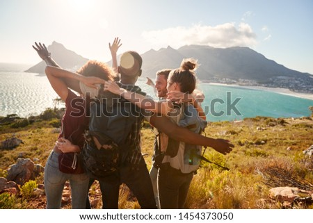 Young adult friends on a hike celebrate reaching a summit near the coast together #1454373050
