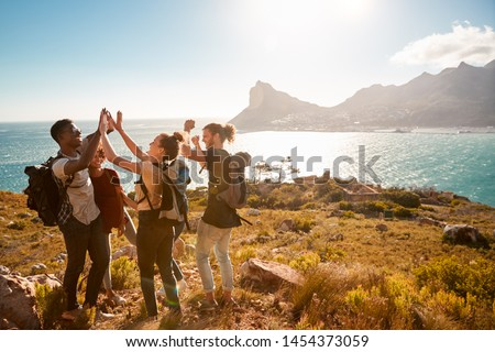 Young adult friends on a hike celebrate reaching a summit near the coast, full length, side view #1454373059