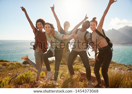 Millennial friends on a hiking trip celebrate reaching the summit and have fun posing for photos #1454373068